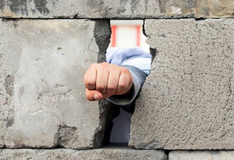 De man hand in een vuist wordt gedrukt breekt door de muur van grijze concrete blokken dat Symbool van strijd, overwinning en bev stock fotografie