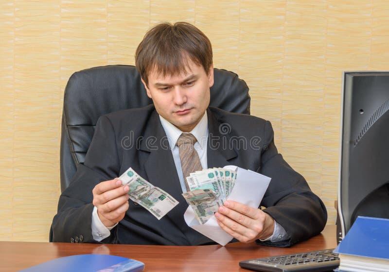 De man in het bureau trekt ernstig geld uit de envelop stock afbeeldingen