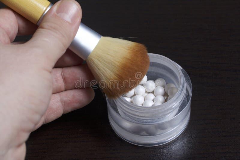 De man houdt een borstel om schoonheidsmiddelen toe te passen Het wordt verminderd met een uiteinde in een ronde kruik met een pa stock afbeeldingen
