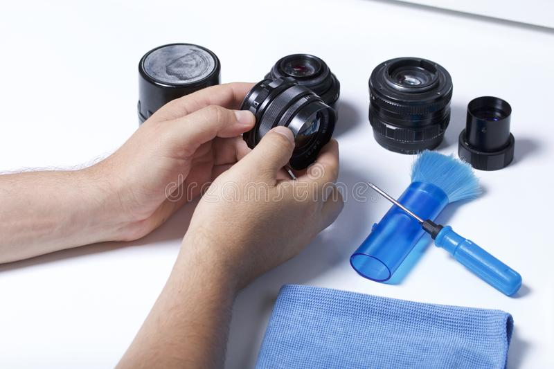 De man houdt een oude lens in zijn handen Dichtbij op de lijst lig andere uitstekende lenzen en apparaten voor reparatie en onder stock fotografie