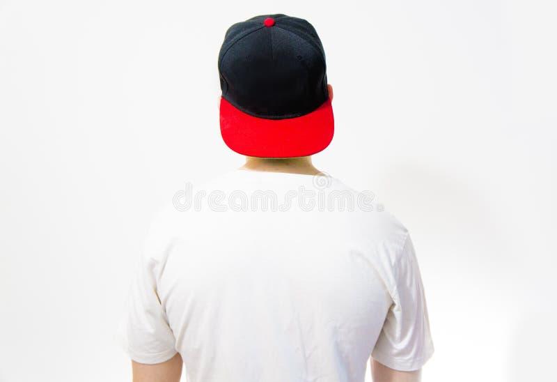 De man, kerel in het lege zwarte, rode honkbal GLB, op een witte achtergrond met witte omhoog t-shirt, spot, vrije ruimte, emblee royalty-vrije stock afbeelding