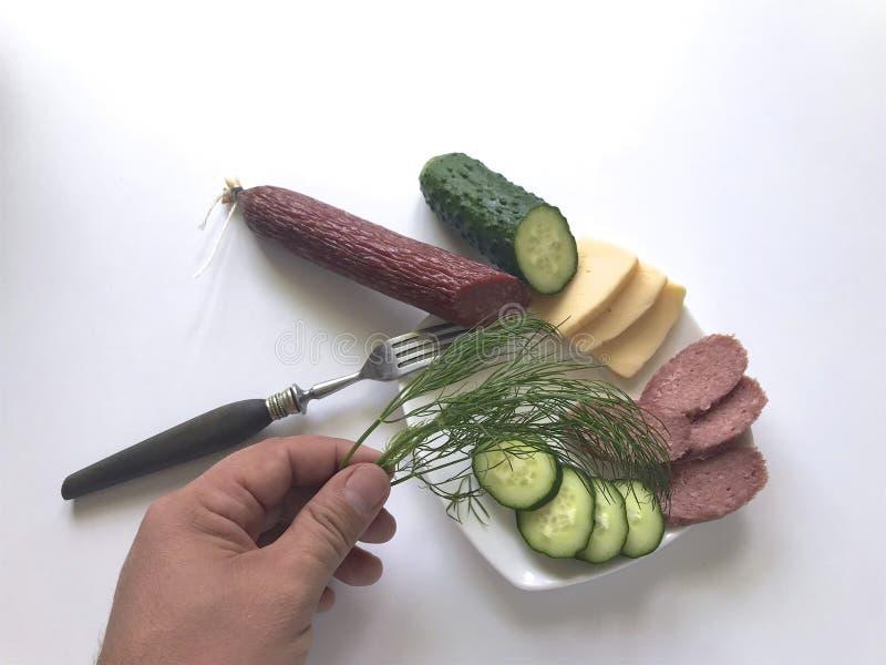 De man maakt een gemakkelijke snack Op de schotel zijn worst, komkommer, kaas en dille royalty-vrije stock foto's