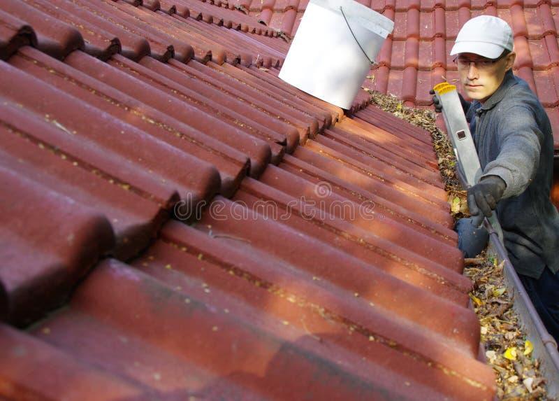 De man maakt de goten op het dak schoon stock foto's