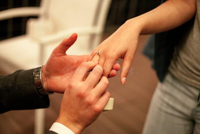 De man maakt vrouwenaanzoek en zet op verlovingsring stock afbeelding