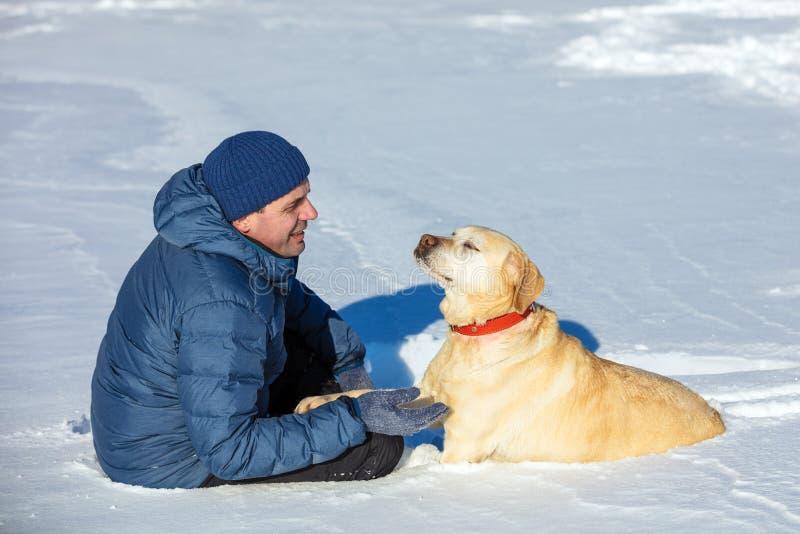 De man met de hondzitting op een sneeuwgebied in de winter royalty-vrije stock foto