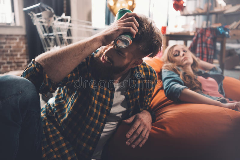 De man met hoofdpijnholding kan van bier, vrouw erachter in slordige ruimte royalty-vrije stock foto's