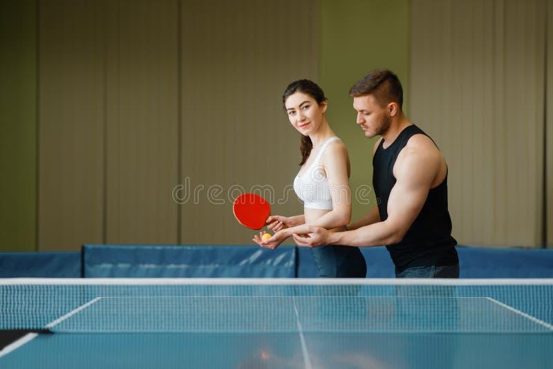 De man onderwijst een vrouw om pingpong te spelen stock fotografie