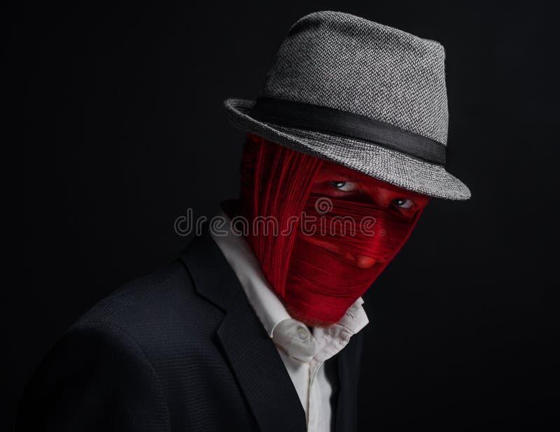 De man op de hoed, met rood draadgezicht wordt gebonden, zwarte achtergrond die stock fotografie