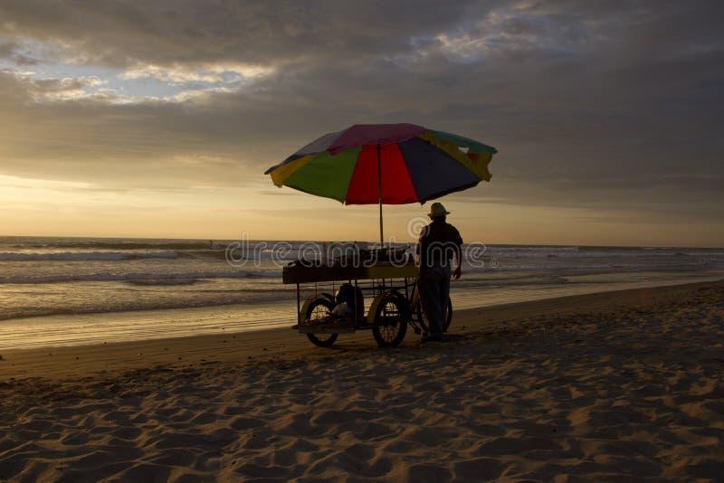 De man op het strand bij zonsondergang stock afbeelding