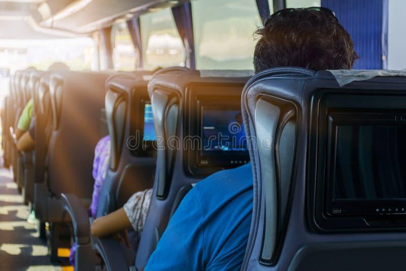 De man op de passagierszetel van de bus luistert aan muziek en bekijkt de tablet Hij bekijkt het apparaten` s scherm en glimlacht royalty-vrije stock afbeeldingen