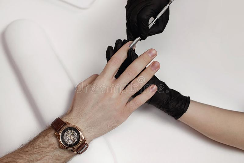 De man op procedures in manicuresalon stock fotografie