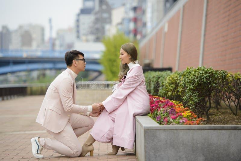 De man op zijn knieën doet een voorstel om de vrouw op de weg te huwen stock foto's