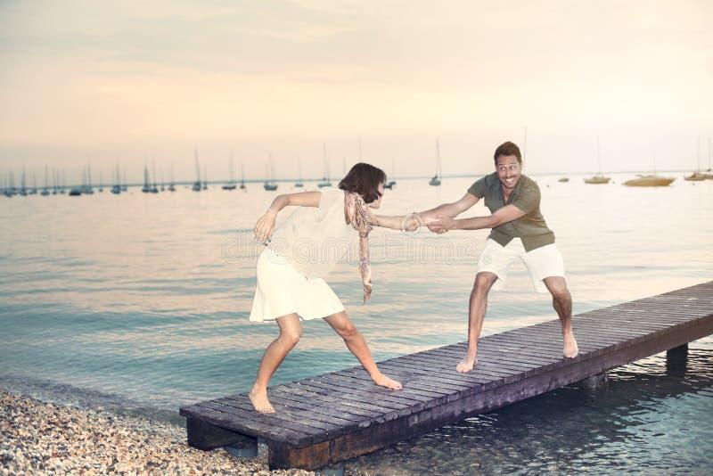 De man probeert om haar vrouw in het water te duwen royalty-vrije stock foto