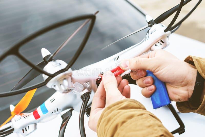 De man sluit de batterij aan de hommel aan alvorens te vliegen stock foto