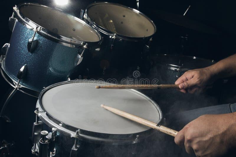 De man speelt drumstel op laag lichtachtergrond stock afbeeldingen