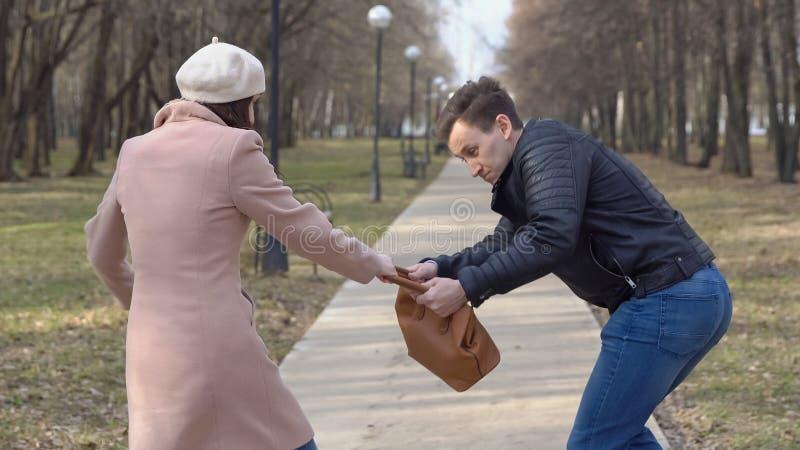 De man steelt een vrouwen` s zak van een bank in het park stock foto's