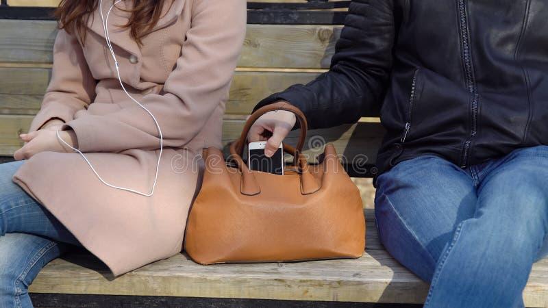 De man steelt de telefoon van een vrouwen` s zak in het park royalty-vrije stock fotografie