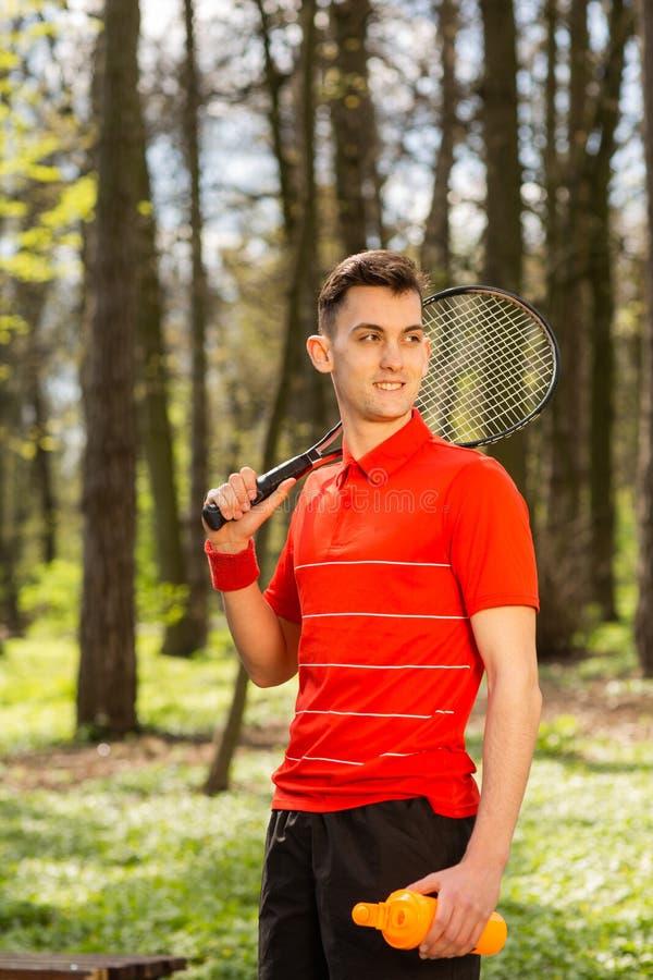 De man stelt met een tennisracket en een oranje thermokoppel, op de achtergrond van groen park Het concept van de sport royalty-vrije stock fotografie