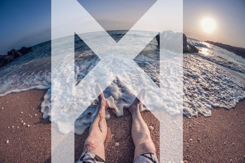 De man symboliseert de rune van mannaz, zit de man op het strand, eerste-persoonsmening, de vervorming van het vissenoog royalty-vrije stock afbeeldingen