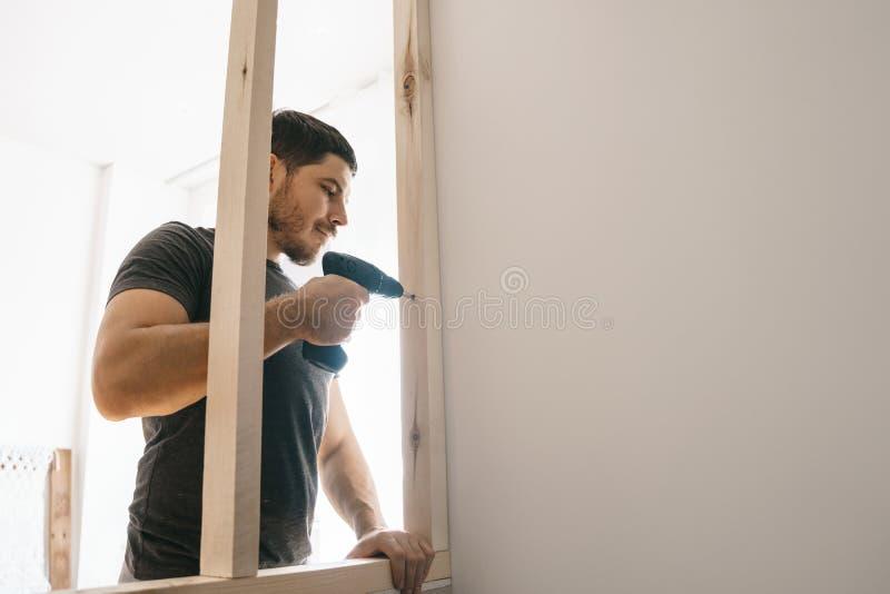 De man is tevreden met de schroevedraaier, bevestigend het houten kader voor het venster aan de lichte muur Reparatie zelf stock afbeelding