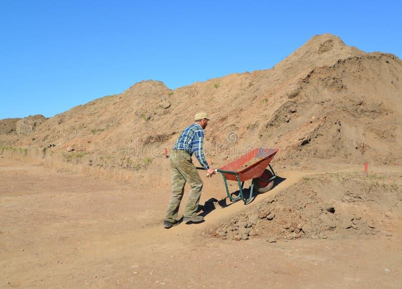 De man van gemiddelde jaren is gelukkig een kruiwagen met grond op roa royalty-vrije stock foto's