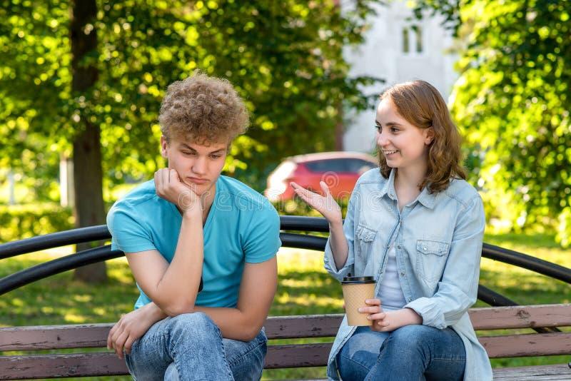 De man is vermoeid van het spreken Het meisje spreekt aan de kerel Tegenzin om aan de gesprekspartner te luisteren Een kerel met  stock foto