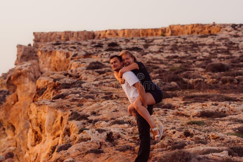 De man vervoert terug vrouw op in de avond op de rots stock afbeeldingen