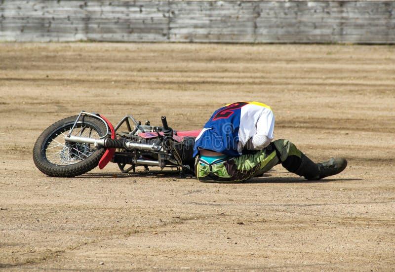 De man viel van een motorfiets en houdt op de buik, trauma bij een verkeerongeval, spel royalty-vrije stock afbeeldingen