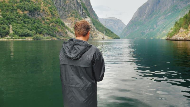 De man vist op de achtergrond van de bergen in de schilderachtige fjord van Noorwegen Visserij in het concept van Noorwegen royalty-vrije stock foto's