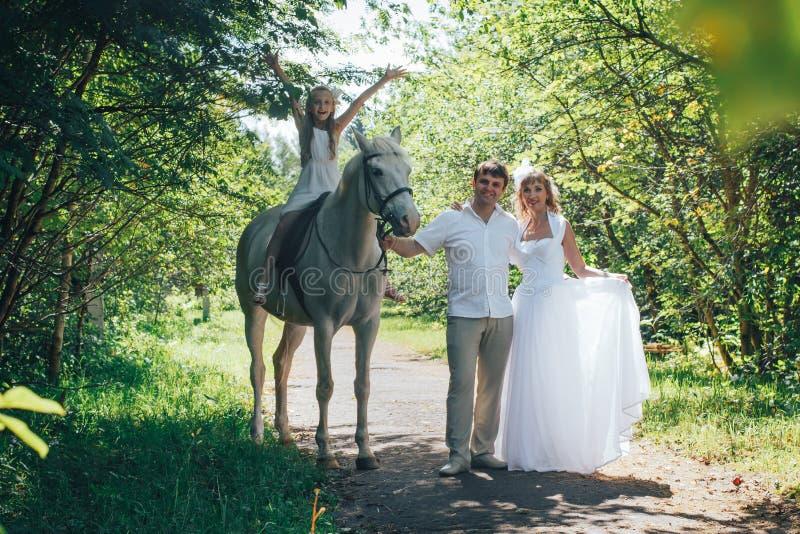 De man, vrouw kleedde zich als bruid, meisje en wit paard in het park stock afbeelding