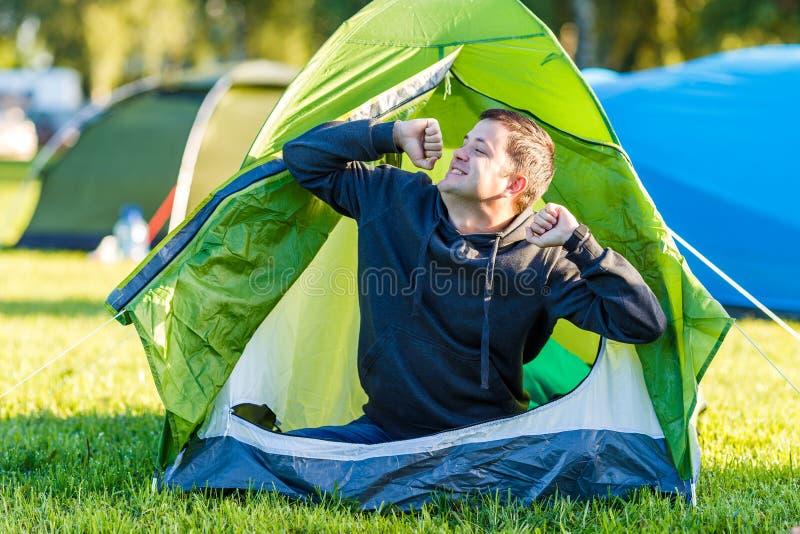 De man wekte, ging zitten en rekte zich in de tent uit stock foto