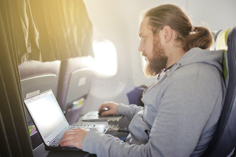 De man werkt achter laptop in salon het vliegtuig royalty-vrije stock afbeeldingen