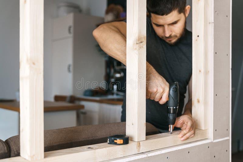 De man werkt als schroevedraaier, bevestigend een houten kader voor het venster aan de verdeling van de gipsgipsplaat royalty-vrije stock foto's