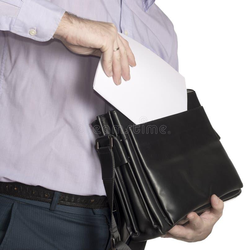 De man zet een blad van Witboek in zijn aktentas Plaats voor tekst isoleer royalty-vrije stock fotografie