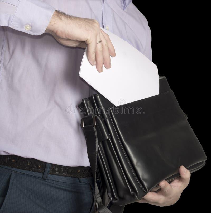 De man zet een blad van Witboek in zijn aktentas Plaats voor tekst Isoleer op zwarte stock afbeeldingen
