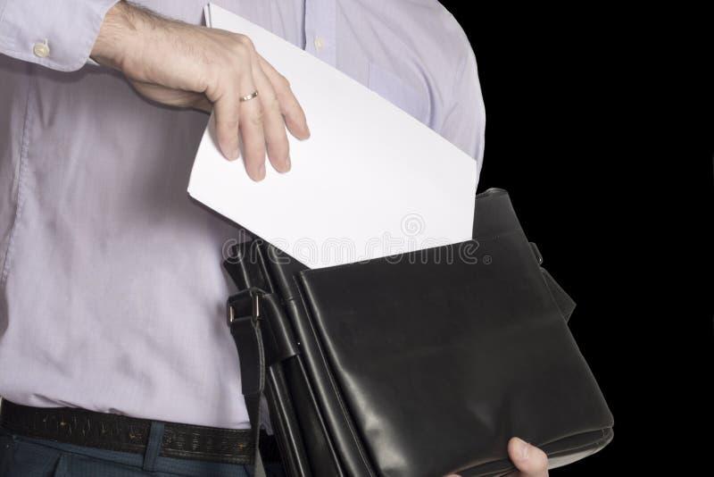 De man zet een blad van Witboek in zijn aktentas Plaats voor tekst Isoleer op zwarte stock foto's