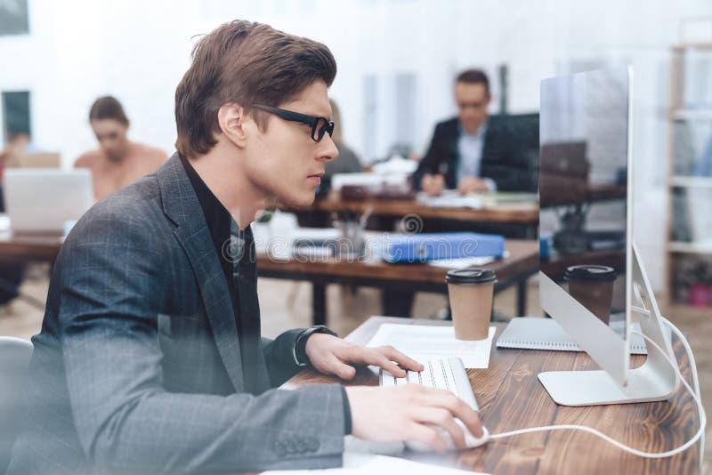 De man zit bij de computer stock foto