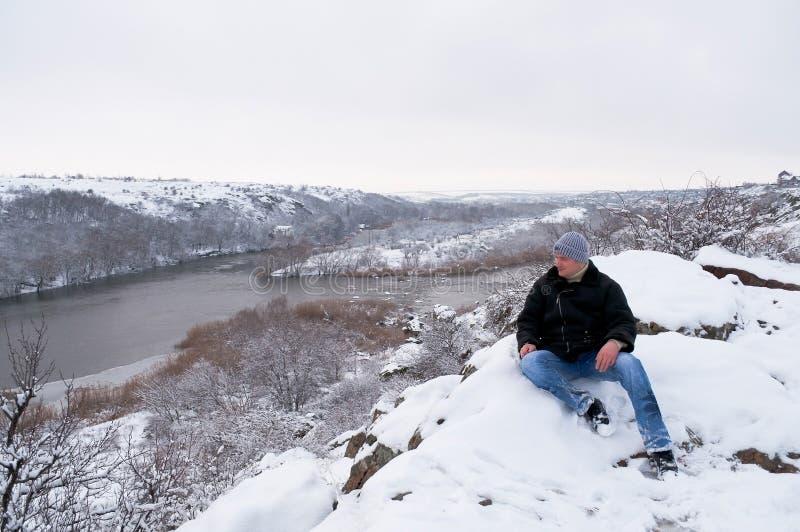 De man zit op een snow-covered rots royalty-vrije stock foto's
