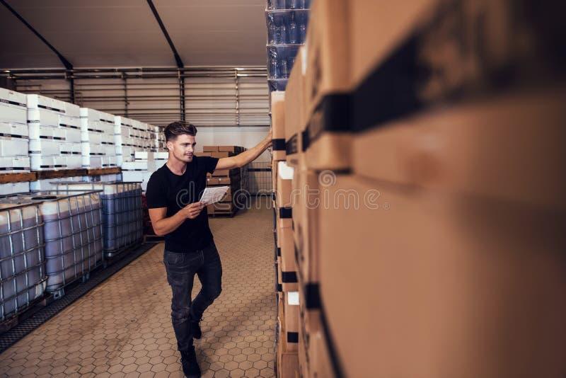 De manager die van het brouwerijpakhuis inventaris nemen stock fotografie