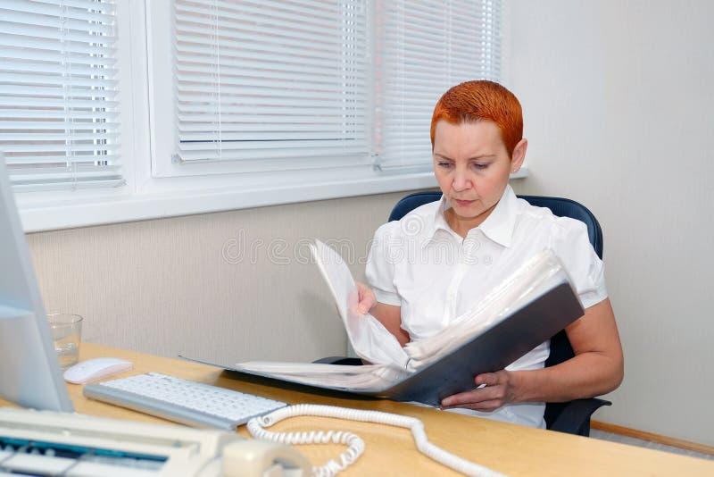 De Manager die van het meisjesbureau documenten bekijken geconcentreerd stock afbeelding