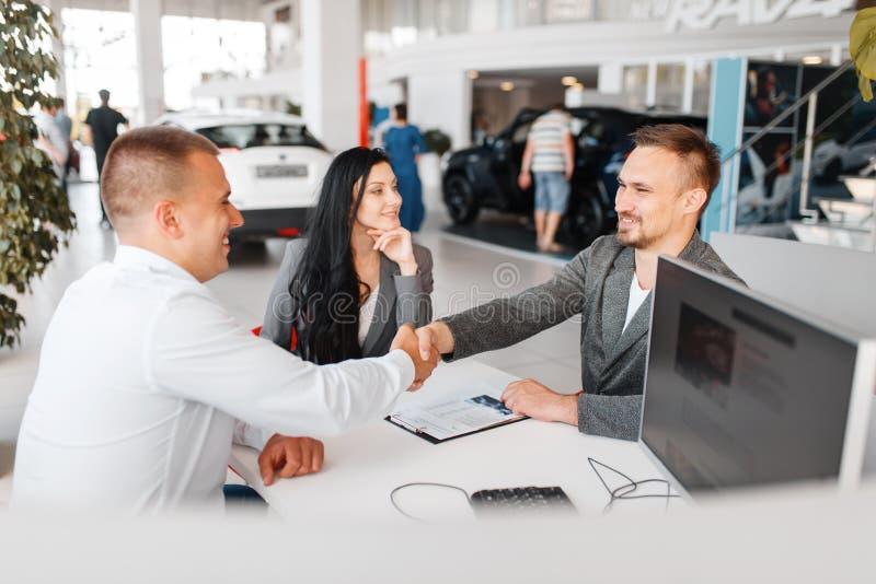 De manager en het paar maken de verkoop van een nieuwe auto op royalty-vrije stock afbeelding