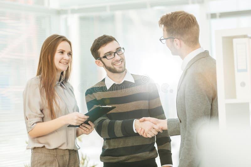 De manager schudt handen met de werknemer in een werkplaats in een modern bureau stock foto
