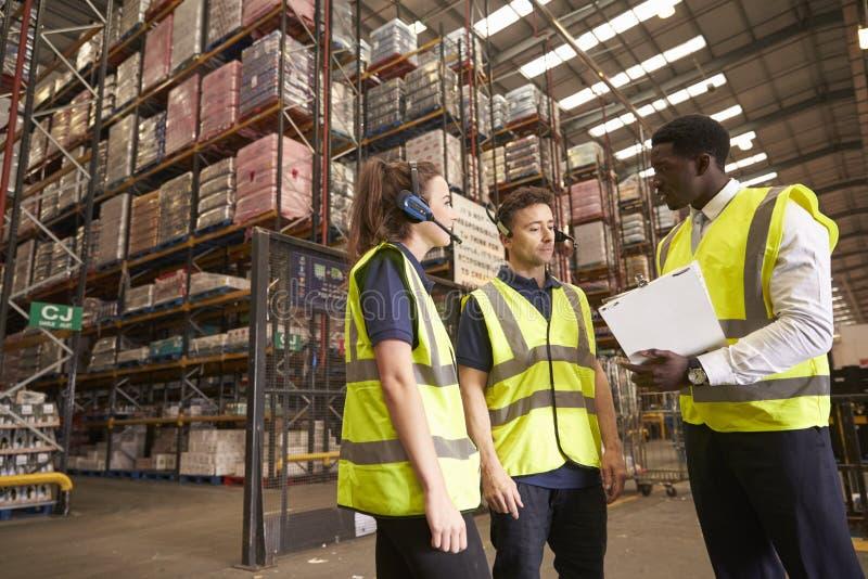 De manager van het distributiepakhuis in bespreking met collega's stock fotografie