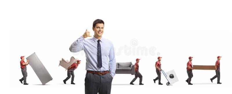 De manager van verwijderingsbedrijf het gesturing roept ons teken en arbeiders die meubilair en appliences dragen royalty-vrije stock foto