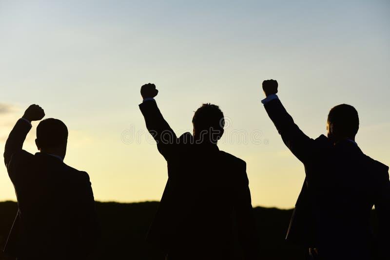 De managers die slimme kostuums dragen bewonderen mening Bedrijfs en succesconcept De leiders bespreken omhoog, de handen van de  stock afbeelding