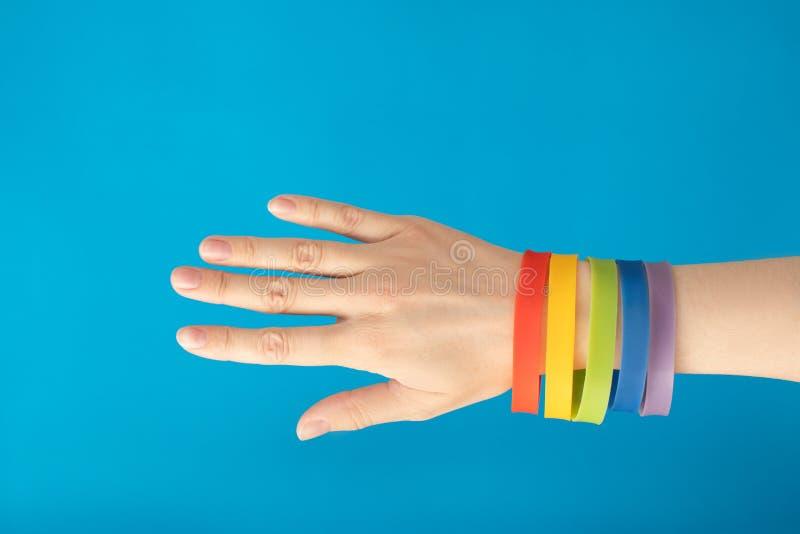 De manchetarmband van de regenboogvlag LGBT op vrouwelijke hand op blauwe achtergrond stock afbeelding
