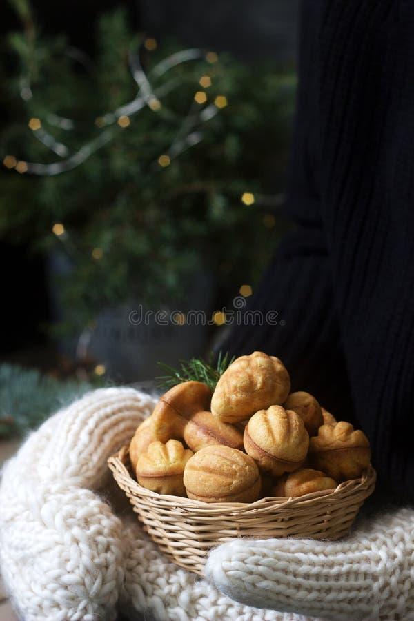 De mand met eigengemaakte zandkoekkoekjes in wijfje dient vuisthandschoenen op een feestelijke achtergrond in royalty-vrije stock fotografie