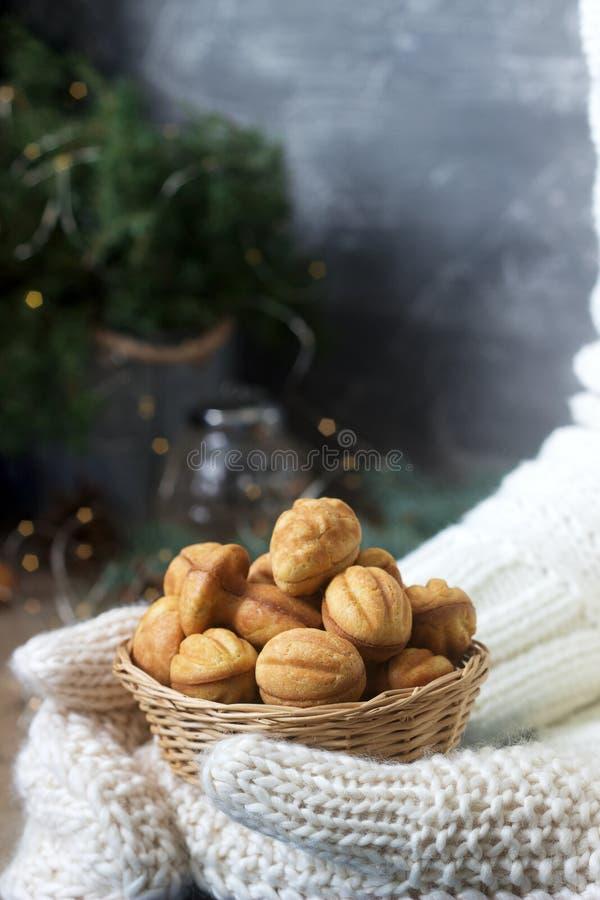 De mand met eigengemaakte zandkoekkoekjes in wijfje dient vuisthandschoenen op een feestelijke achtergrond in stock afbeelding