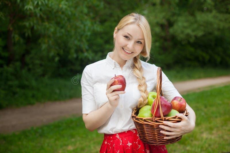 De mand van de meisjesholding met rode en groene appelen in het park stock fotografie