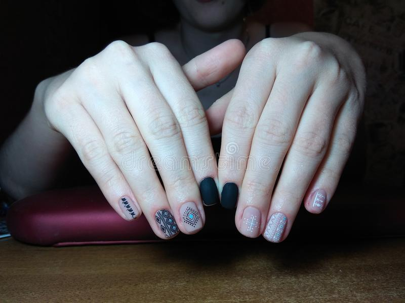 De manicure maakte uitstekend tot haar werk een mooie manicure met een poetsmiddelgel op haar handen en de cliënt is gelukkig stock afbeelding